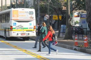 Pedestres passam no meio da via ao descer do ônibus nos corredores  Crédito: Vinicius Roratto