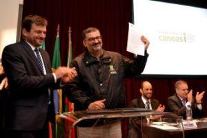 Prefeito Jairo Jorge mostra a Ordem de Serviço assinada com o diretor da Aeromovel Brasil, Marcus Coester.